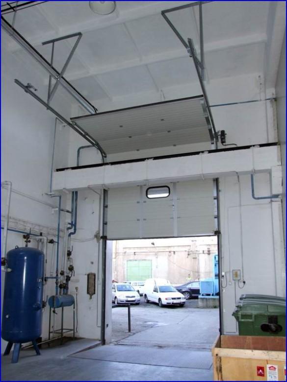 Emelt sínvezetésű ipari kapu referencia a Greensolar Kft-nél, beépített ajtóval